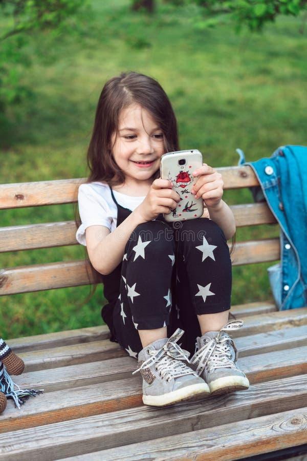 Niña con un smartphone que se sienta en un banco imagen de archivo