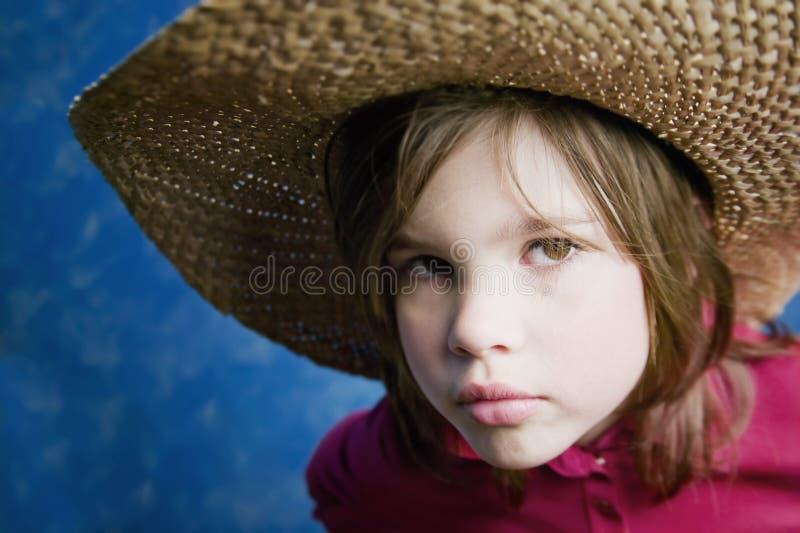 Niña con un sombrero de paja imagen de archivo