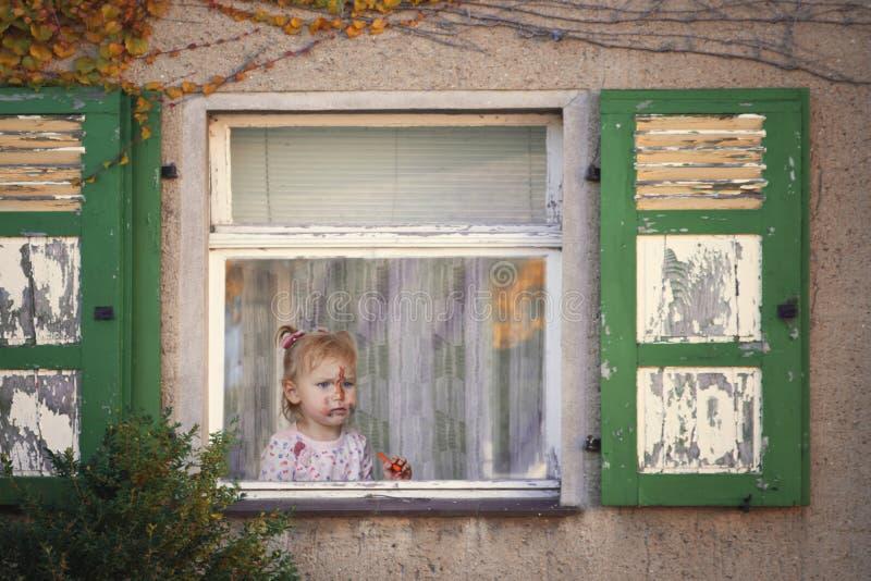 Niña con una cara manchada, mirando para arriba de la ventana de a imagenes de archivo