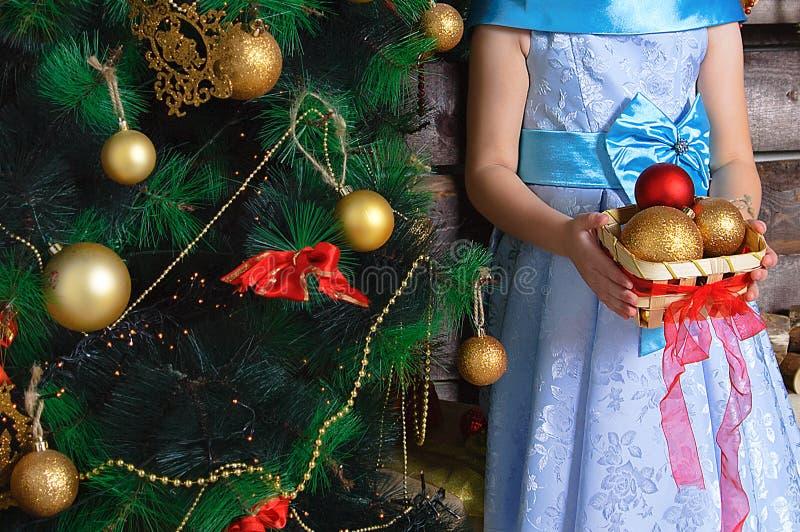 Niña con una cesta de decoraciones de la Navidad Se coloca cerca del árbol de navidad fotografía de archivo