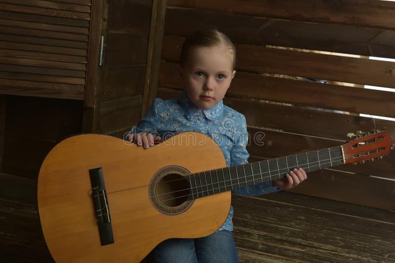 Niña con una guitarra foto de archivo