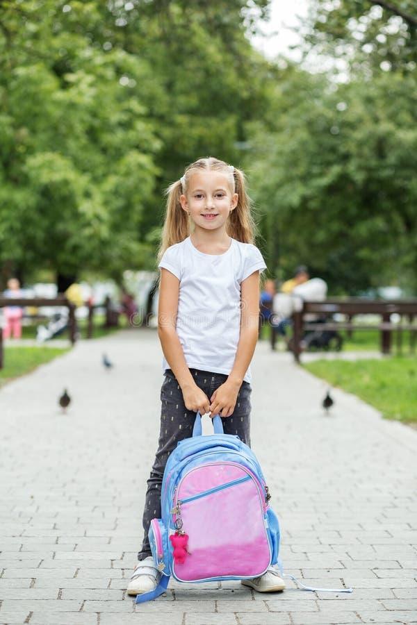 Niña con una mochila en el patio El concepto de escuela, estudio, educación, niñez imagen de archivo libre de regalías