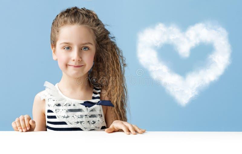 Niña con una nube en forma de corazón foto de archivo libre de regalías