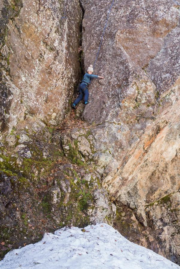 Niña contratada a los deportes que suben la roca natural, vertical foto de archivo
