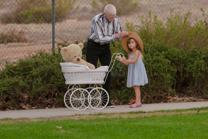 Niña de ayuda del abuelo con el sombrero en paseo con el cochecillo del juguete imagenes de archivo