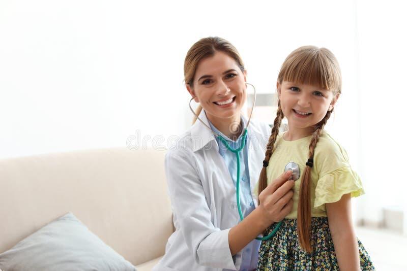 Niña de examen del doctor de los niños en casa imagenes de archivo
