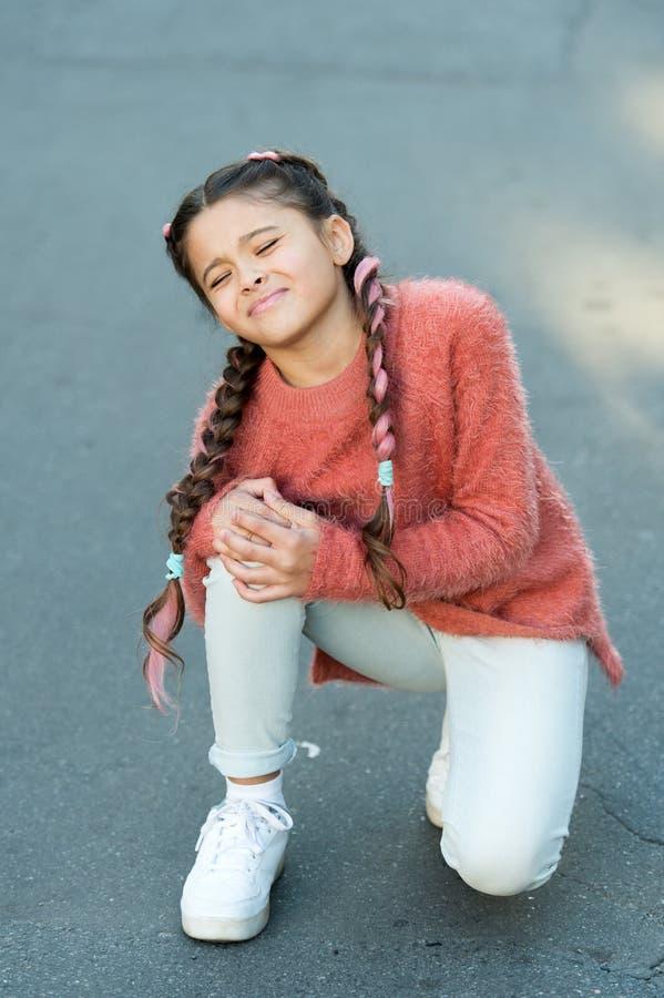 niña de grito en suéter del otoño El pequeño niño tiene dolor en rodilla El otoño se acurruca Moda del otoño para la muchacha bon imágenes de archivo libres de regalías