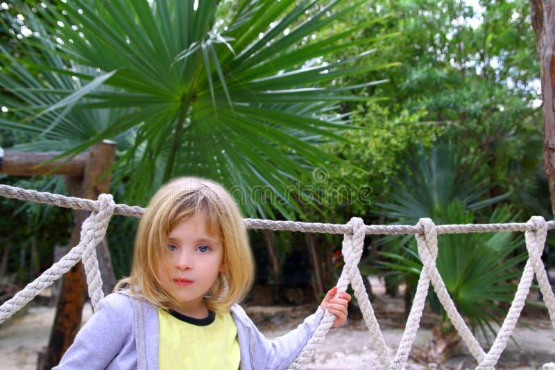 Niña de la aventura en el puente de cuerda del parque de la selva foto de archivo