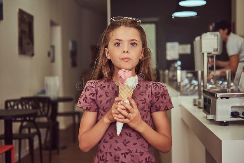 Niña de la belleza en un vestido de moda que come la fresa, colocándose en una sala de helado imágenes de archivo libres de regalías