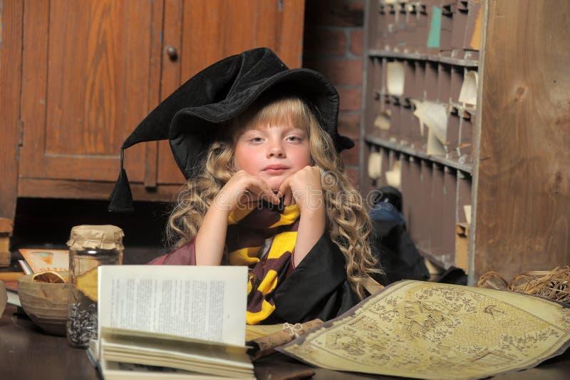 Niña de la bruja con el libro de la pila imagen de archivo libre de regalías