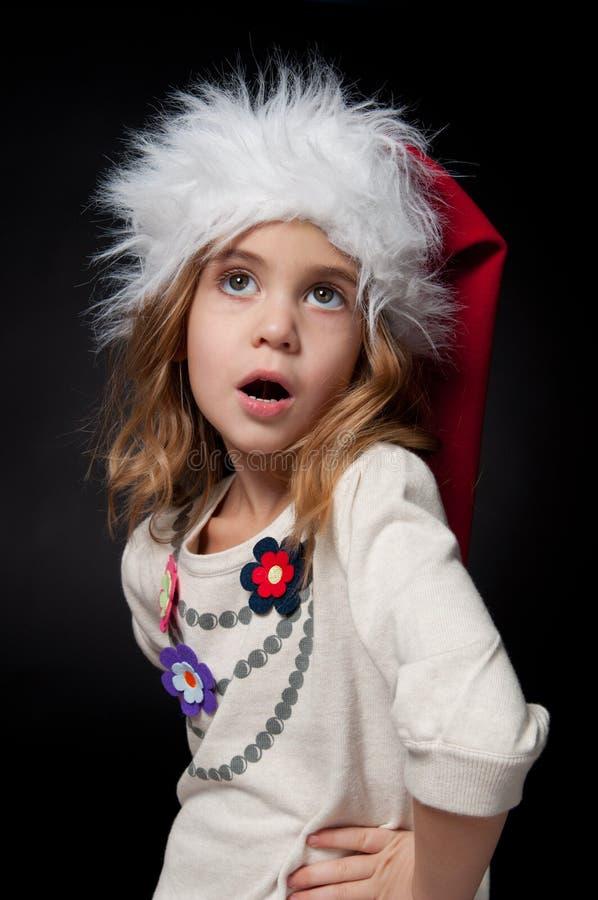 Niña de moda hermosa que lleva el sombrero de Papá Noel imágenes de archivo libres de regalías