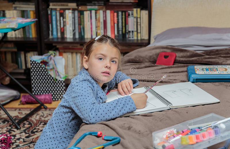 niña de moda hermosa que se sienta en su sitio y que hace a casa el trabajo imágenes de archivo libres de regalías