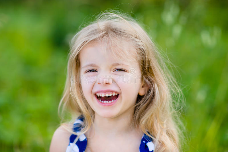Niña de risa adorable con el pelo rizado rubio largo, imagenes de archivo