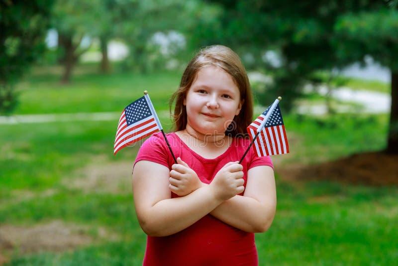 Niña de risa con el pelo rubio rizado largo que celebra la bandera americana y agitarla, retrato al aire libre el día soleado en  foto de archivo