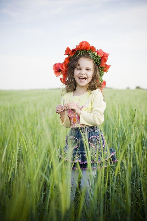 Niña de risa en guirnalda floral fotos de archivo libres de regalías
