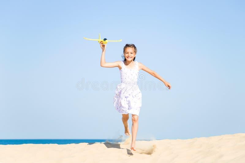 Niña de risa feliz linda que lleva un vestido blanco que corre en la playa arenosa por el mar y que juega con imagen de archivo