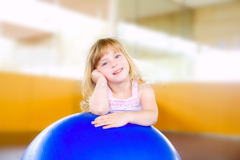 Niña del niño con la bola de los aeróbicos de la gimnasia imagen de archivo