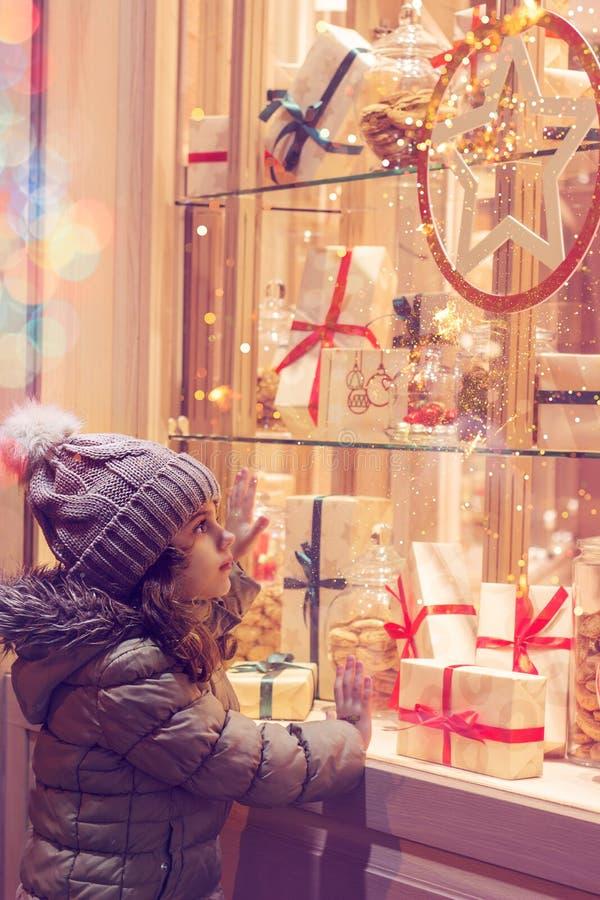 Niña delante de la ventana de una tienda, llena de regalos envueltos fotografía de archivo