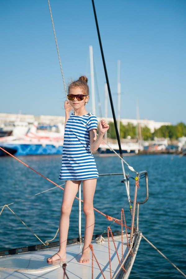 Niña delgada hermosa en una camiseta rayada y gafas de sol a bordo del barco de lujo imagen de archivo libre de regalías
