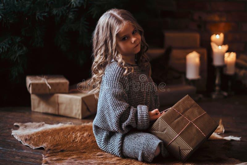 Niña descontenta con el pelo rizado rubio que lleva un suéter caliente que se sienta en un piso rodeado por los regalos al lado d fotografía de archivo libre de regalías
