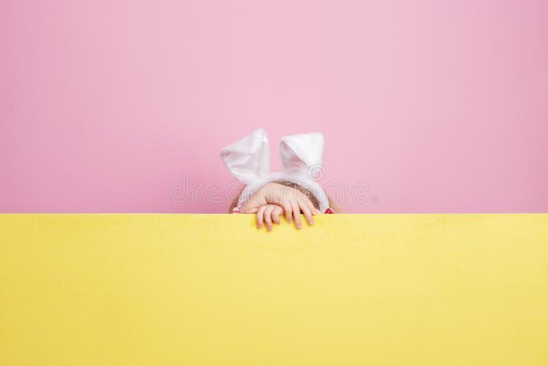 Niña divertida con los oídos del conejito en sus pieles principales detrás del tablero amarillo contra una pared rosada imagen de archivo libre de regalías