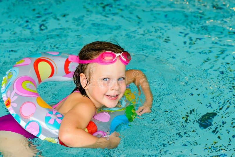 Niña divertida en gafas rosadas en la piscina fotografía de archivo libre de regalías