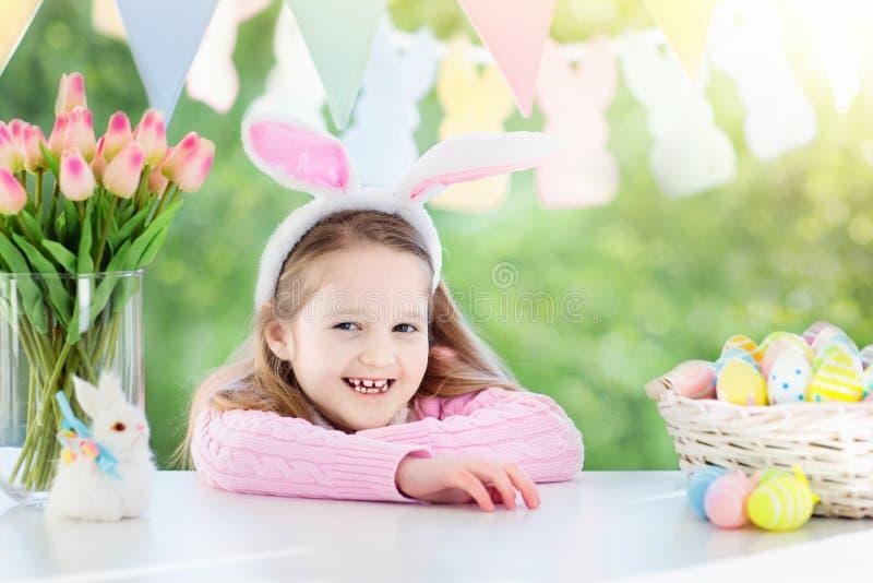Niña divertida en oídos del conejito en el desayuno el la mañana de Pascua en la tabla con los huevos de Pascua fotografía de archivo