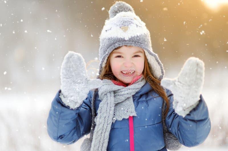 Niña divertida que se divierte en parque hermoso del invierno durante las nevadas fotos de archivo