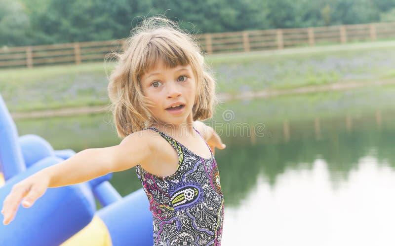 Niña divertida que se divierte en paseos inflables en el lago Concepto de las vacaciones de verano foto de archivo