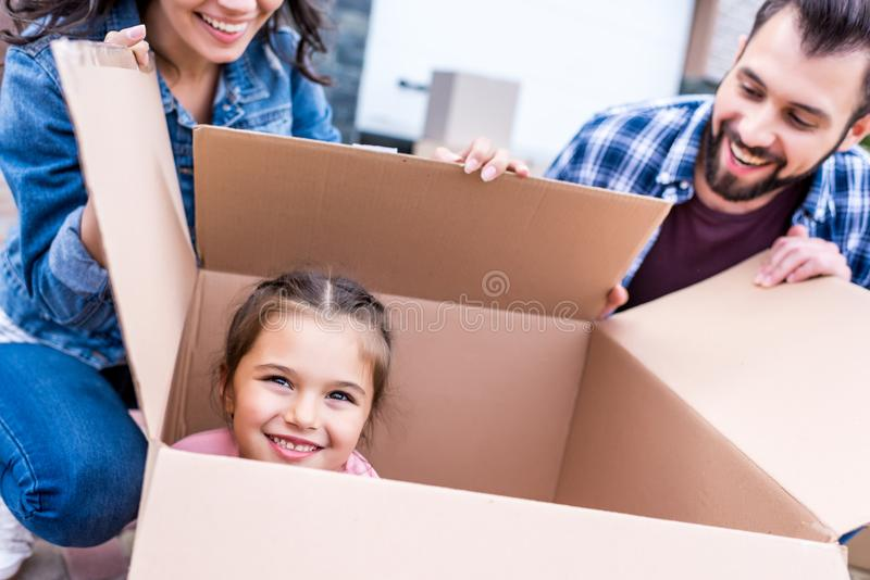 niña divertida que se sienta en caja de cartón mientras que mirada feliz de los padres imagen de archivo