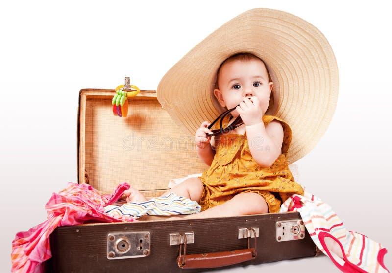 Niña divertida que se sienta en maleta vieja foto de archivo libre de regalías