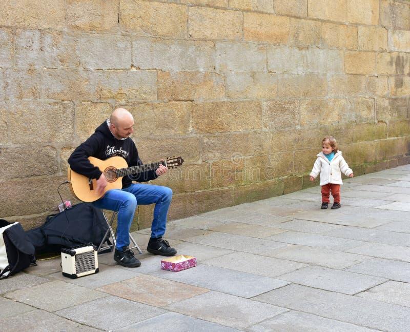 Niña divertida y hombre que tocan la guitarra en una calle cerca de la catedral Santiago de Compostela, España, el 22 de febrero  foto de archivo