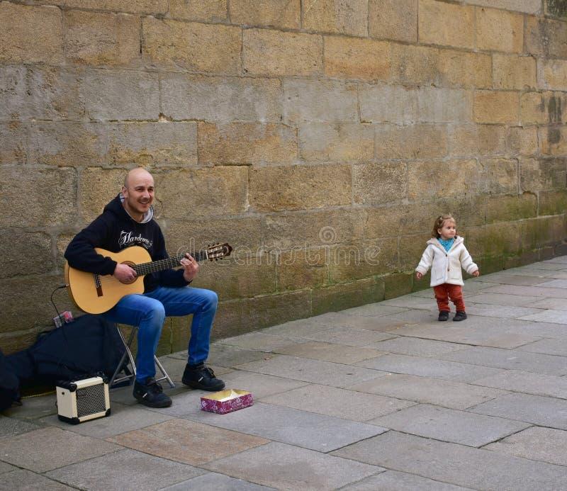 Niña divertida y hombre que tocan la guitarra en una calle cerca de la catedral Santiago de Compostela, España, el 22 de febrero  fotos de archivo libres de regalías