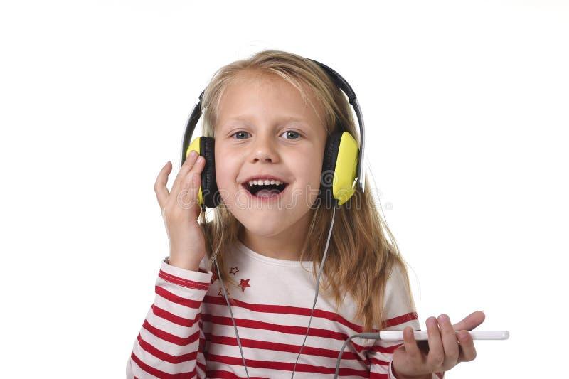 Niña dulce con el pelo rubio que escucha la música con los auriculares y el teléfono móvil que canta y que baila feliz fotos de archivo