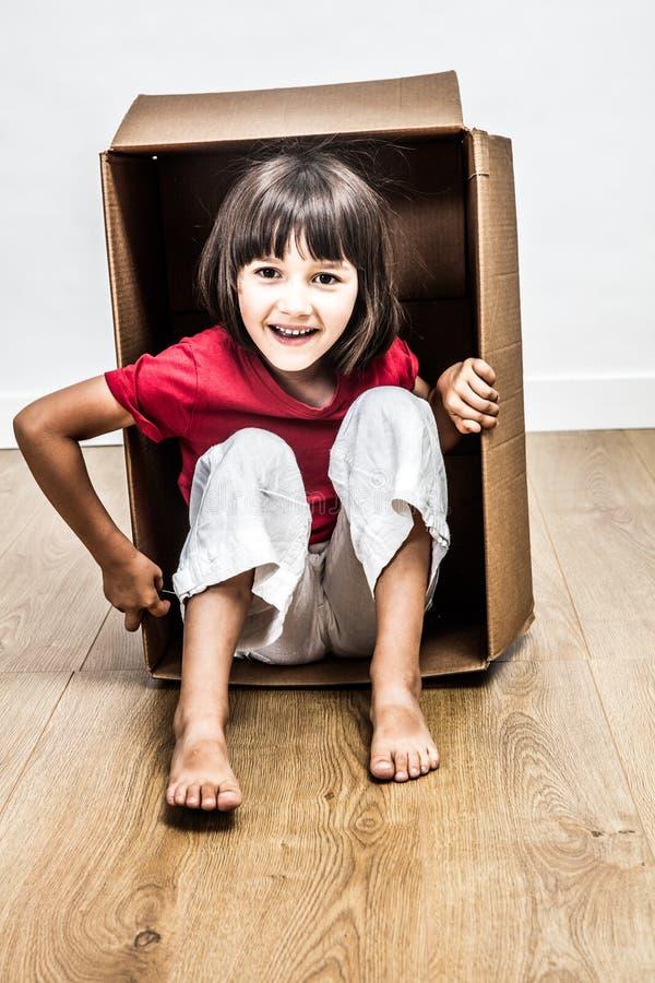 Niña emocionada que se sienta en la caja de cartón que juega para la sorpresa fotos de archivo