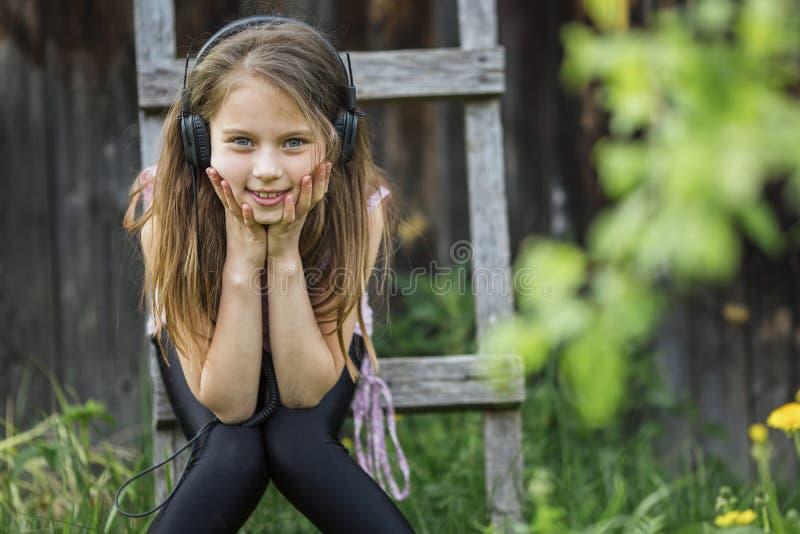 Niña en auriculares que disfruta de música en naturaleza imagen de archivo
