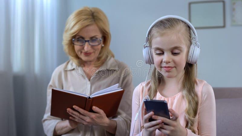 Niña en auriculares que escucha la lectura mayor de la abuela de la mujer del expediente de libro fotos de archivo