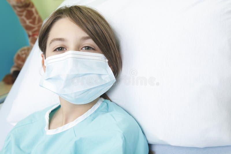 Niña en cama de hospital fotos de archivo