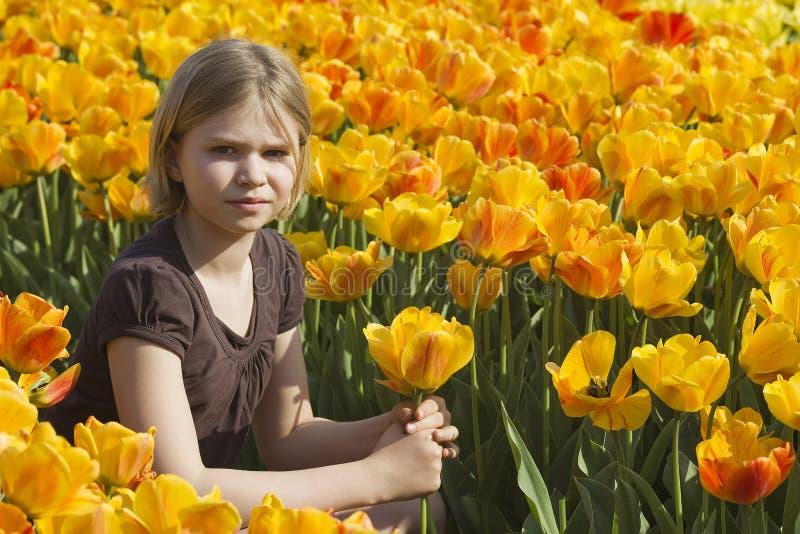 Niña en campo de los tulipanes imagen de archivo