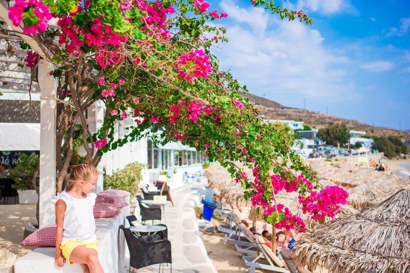 Niña en el café de la playa con vista al mar y ociosos en las vacaciones europeas fotos de archivo libres de regalías