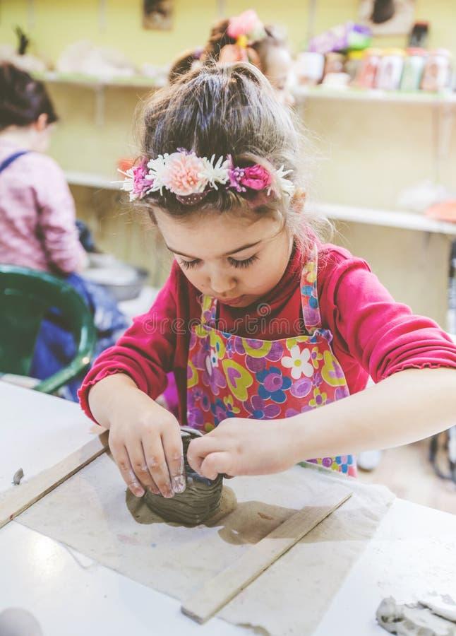 Niña en el funcionamiento del taller de la cerámica con la arcilla fotos de archivo libres de regalías