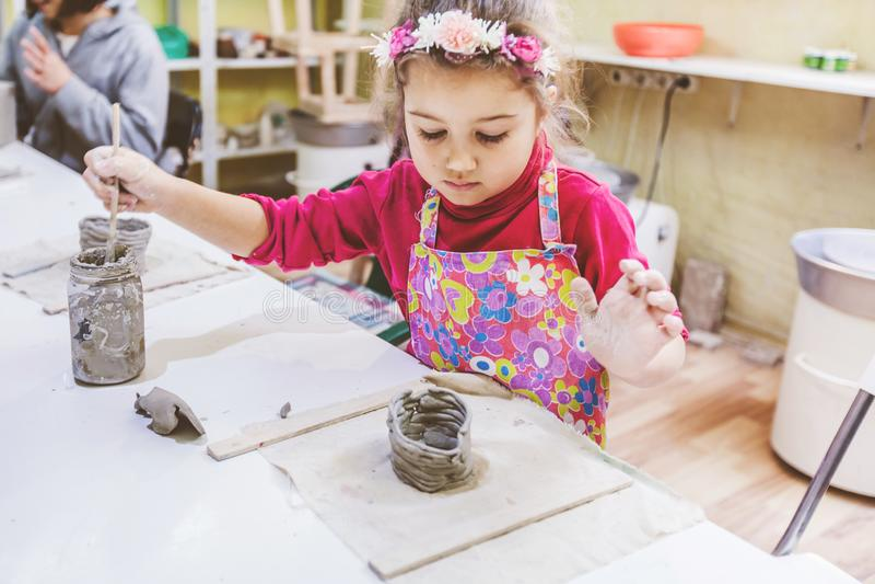 Niña en el funcionamiento del taller de la cerámica con la arcilla imagen de archivo
