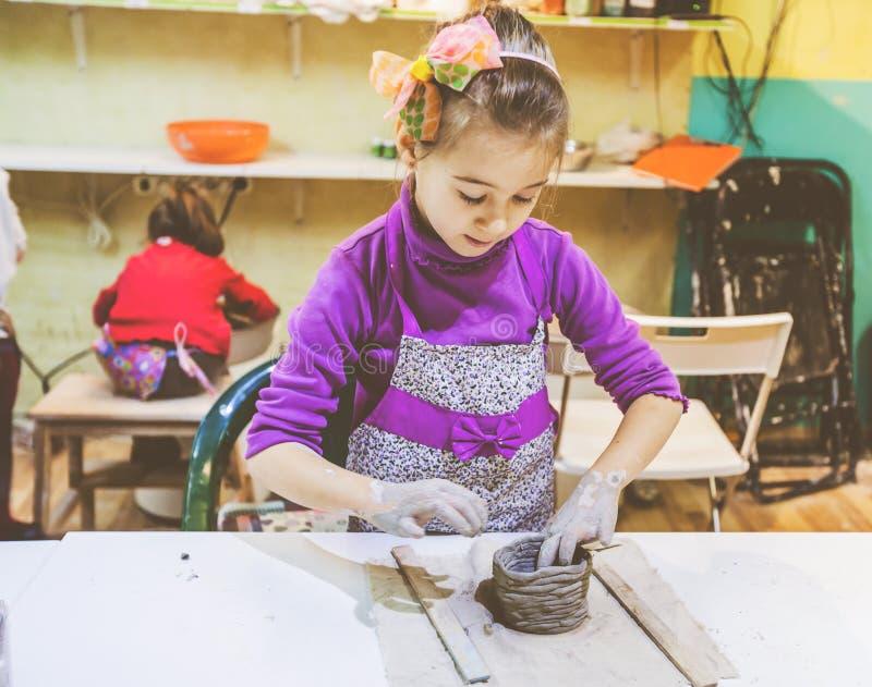 Niña en el funcionamiento del taller de la cerámica con la arcilla imágenes de archivo libres de regalías