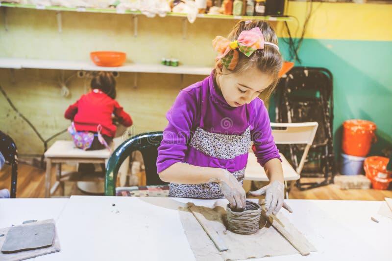 Niña en el funcionamiento del taller de la cerámica con la arcilla fotografía de archivo