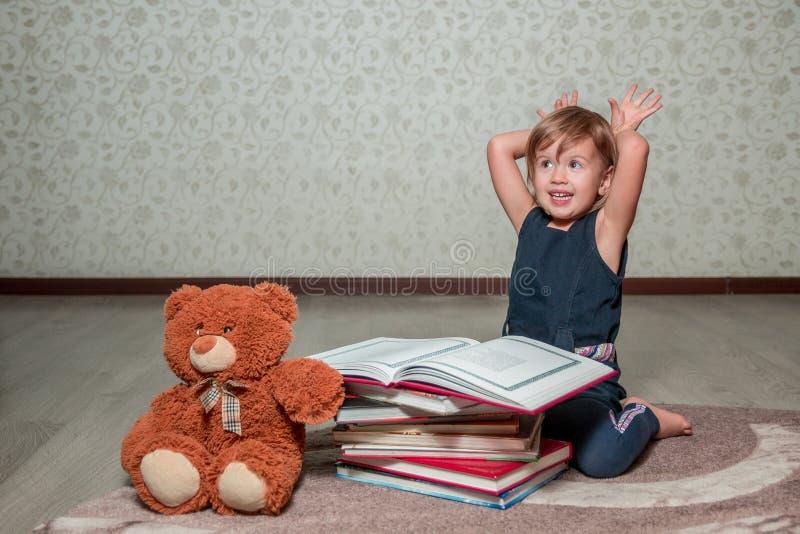niña en el libro de lectura azul marino del vestido que se sienta en el piso cerca de oso de peluche El niño lee la historia para foto de archivo libre de regalías