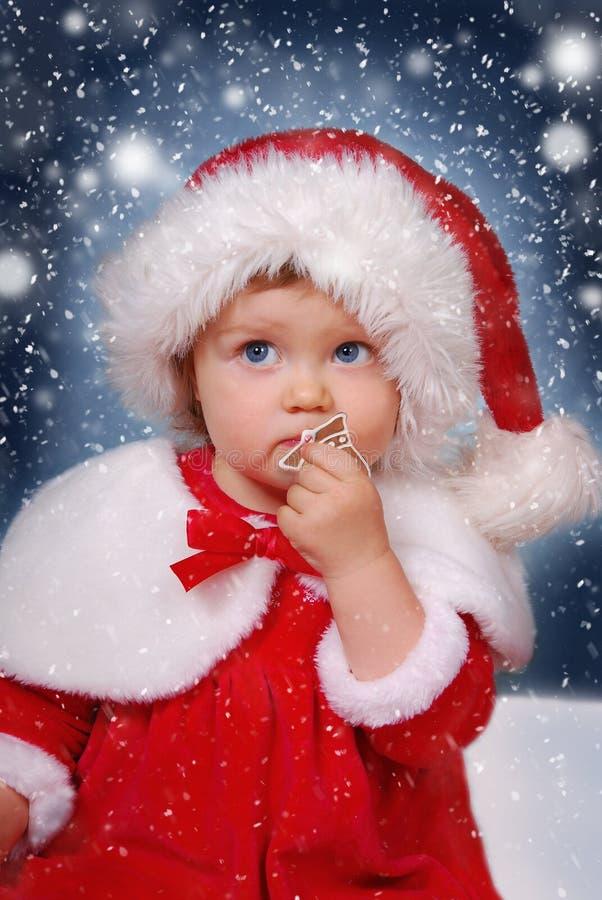 Niña en el sombrero de santa el noche de la Navidad imagenes de archivo