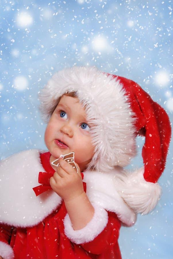Niña en el sombrero de santa el tiempo de la Navidad imagenes de archivo