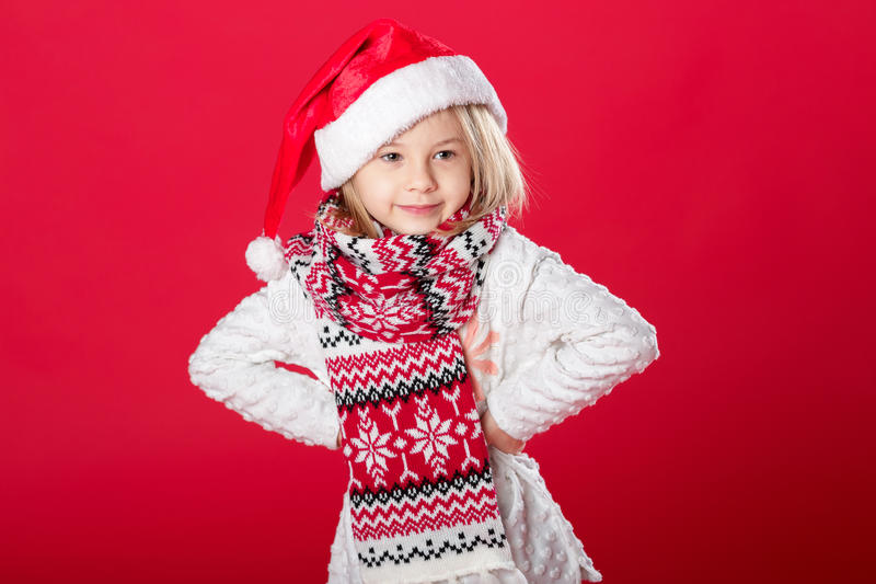 Niña en el sombrero y la bufanda de santa en fondo rojo imágenes de archivo libres de regalías