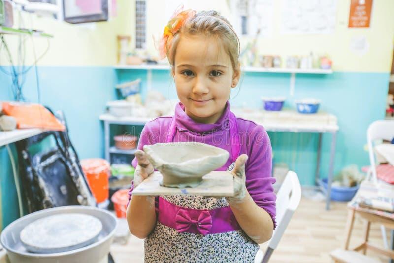 Niña en el taller de la cerámica que muestra a Clay Vase imagen de archivo