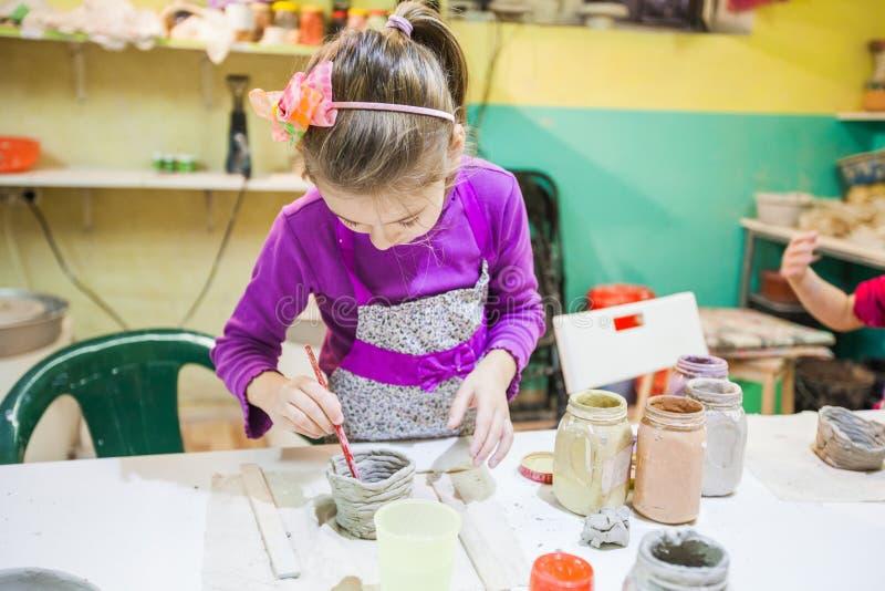 Niña en el taller de la cerámica que pinta a Clay Vase imagen de archivo libre de regalías